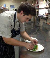 kucharz przyrządzający potrawę w restauracji